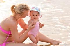 Madre con un bambino sulla spiaggia Immagini Stock