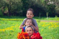 Madre con un campo di due tulipani dei figli in rosso immagini stock