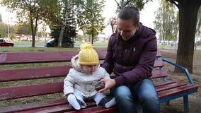 Madre con un fare da baby-sitter su un banco di parco La mamma mostra al vostro bambino uno smartphone stock footage