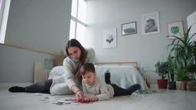 Madre con un niño en el interior blanco de su hogar para recoger el rompecabezas así como su hijo joven Feliz almacen de metraje de vídeo