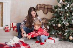 Madre con un piccolo albero di Natale dei regali della decorazione di Natale del bambino fotografia stock