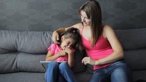 Madre con un uso del niño una tableta que se sienta en el sofá La mujer cosquillea al bebé que se sienta en el sofá Estropeo dura almacen de video