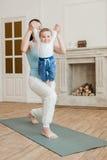 Madre con yoga di pratica del neonato sulla stuoia di yoga Immagini Stock Libere da Diritti