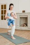 Madre con yoga di pratica del neonato sulla stuoia di yoga Fotografie Stock
