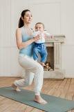 Madre con yoga di pratica del neonato sulla stuoia di yoga Fotografia Stock