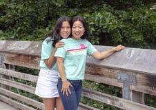 Madre coreana con su hija adolescente que presenta en un puente de madera en Washington Park Arboretum, Seattle, Washington fotografía de archivo