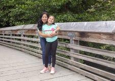 Madre coreana que presenta cariñosamente con su hija en un puente de madera en Washington Park Arboretum, Seattle, Washington fotografía de archivo libre de regalías
