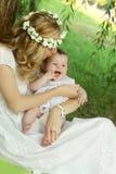Madre in corona che bacia neonata Fotografia Stock