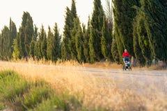 Madre corrente con il passeggiatore di bambino che gode del paesaggio di tramonto Immagine Stock Libera da Diritti