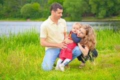 Madre d'abbraccio del bambino e del padre all'aperto Fotografia Stock Libera da Diritti