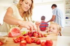 Madre d'aiuto della figlia per preparare la prima colazione della famiglia Fotografie Stock Libere da Diritti