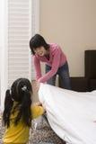 Madre d'aiuto della ragazza nella preparazione del letto Immagine Stock
