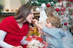 Madre d'alimentazione del ragazzino con i biscotti di Natale Fotografie Stock