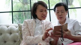 Madre d'istruzione di Daugther per utilizzare Smart Phone per i media sociali a Immagine Stock Libera da Diritti