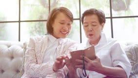Madre d'istruzione di Daugther per utilizzare Smart Phone per i media sociali a Immagini Stock Libere da Diritti