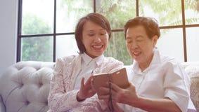 Madre d'istruzione di Daugther per utilizzare Smart Phone per i media sociali a Immagine Stock