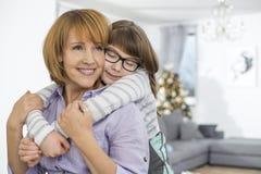 Madre de abarcamiento de la hija cariñosa en casa Foto de archivo libre de regalías