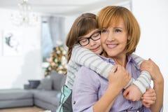 Madre de abarcamiento de la hija cariñosa en casa Fotos de archivo libres de regalías