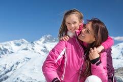 Madre de abarcamiento de la hija en nieve Fotografía de archivo