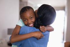 Madre de abarcamiento de la muchacha feliz en sala de estar en casa Fotos de archivo libres de regalías