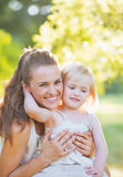 Madre de abarcamiento del bebé al aire libre Imágenes de archivo libres de regalías