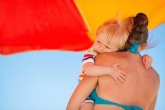 Madre de abarcamiento del bebé en la playa bajo el paraguas Imágenes de archivo libres de regalías