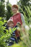 Madre de abarcamiento del muchacho en jardín Imagen de archivo libre de regalías