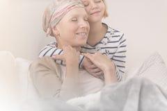 Madre de abarcamiento del niño con leucemia Foto de archivo