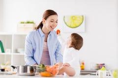 Madre de alimentación del bebé con la cocina de la zanahoria en casa Imagen de archivo