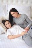 Madre de apoyo que ayuda a su hija adolescente preocupante Foto de archivo libre de regalías