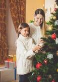 Madre de ayuda del adolescente que adorna el árbol de navidad Imagen de archivo