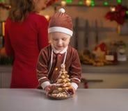 Madre de ayuda del bebé que hace preparaciones de la Navidad en cocina Imagenes de archivo