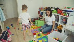 Madre de ayuda de Little Boy al sitio limpio de los juguetes almacen de video
