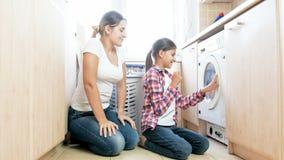 Madre de ayuda sonriente feliz del adolescente en lavadero Fotos de archivo libres de regalías