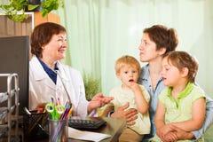 Madre de dos niños que hablan con el doctor del pediatra Fotos de archivo libres de regalías
