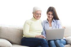 Madre de enseñanza de la mujer cómo utilizar el ordenador portátil fotos de archivo libres de regalías