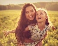 Madre de goce feliz que abraza a su muchacha de risa juguetona del niño en s Fotos de archivo
