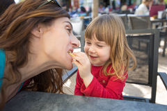 Madre de la alimentación infantil con el soplo del queso en barra exterior Fotografía de archivo libre de regalías