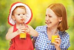 Madre de la familia e hija del bebé que bebe el zumo de naranja en la suma Imagen de archivo