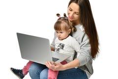 Madre de la familia e hija del niño en casa con un ordenador portátil foto de archivo