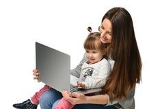 Madre de la familia e hija del niño en casa con un ordenador portátil fotografía de archivo libre de regalías