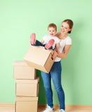 Madre de la familia e hija felices del bebé en un apartamento vacío con Fotos de archivo libres de regalías