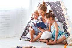 Madre de la familia que lee al libro de niños en tienda en casa Foto de archivo