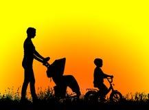 Madre de la silueta con los niños que caminan en la puesta del sol Imagen de archivo