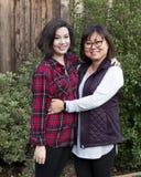 Madre de mediana edad e hija adolescente delante del arbustos verdes Foto de archivo libre de regalías