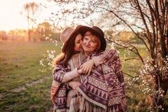 Madre de mediana edad y su hija adulta que abrazan en jardín floreciente Concepto del día del ` s de la madre Valores familiares Foto de archivo