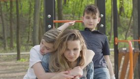 Madre de muchos niños en el parque con sus hijos Los muchachos corren alrededor, uno de ellos que abrazan a la mujer Amistoso gra almacen de video