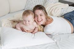 Madre de risa alegre que se relaja en cama con sus 9 meses de b Foto de archivo libre de regalías