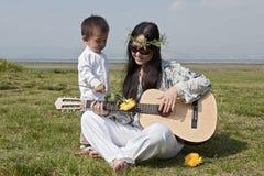 Madre del Hippie que toca la guitarra con el hijo Imagen de archivo