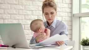 Madre del negocio que trabaja de hogar con el niño Madre con el niño que mira documentos almacen de video